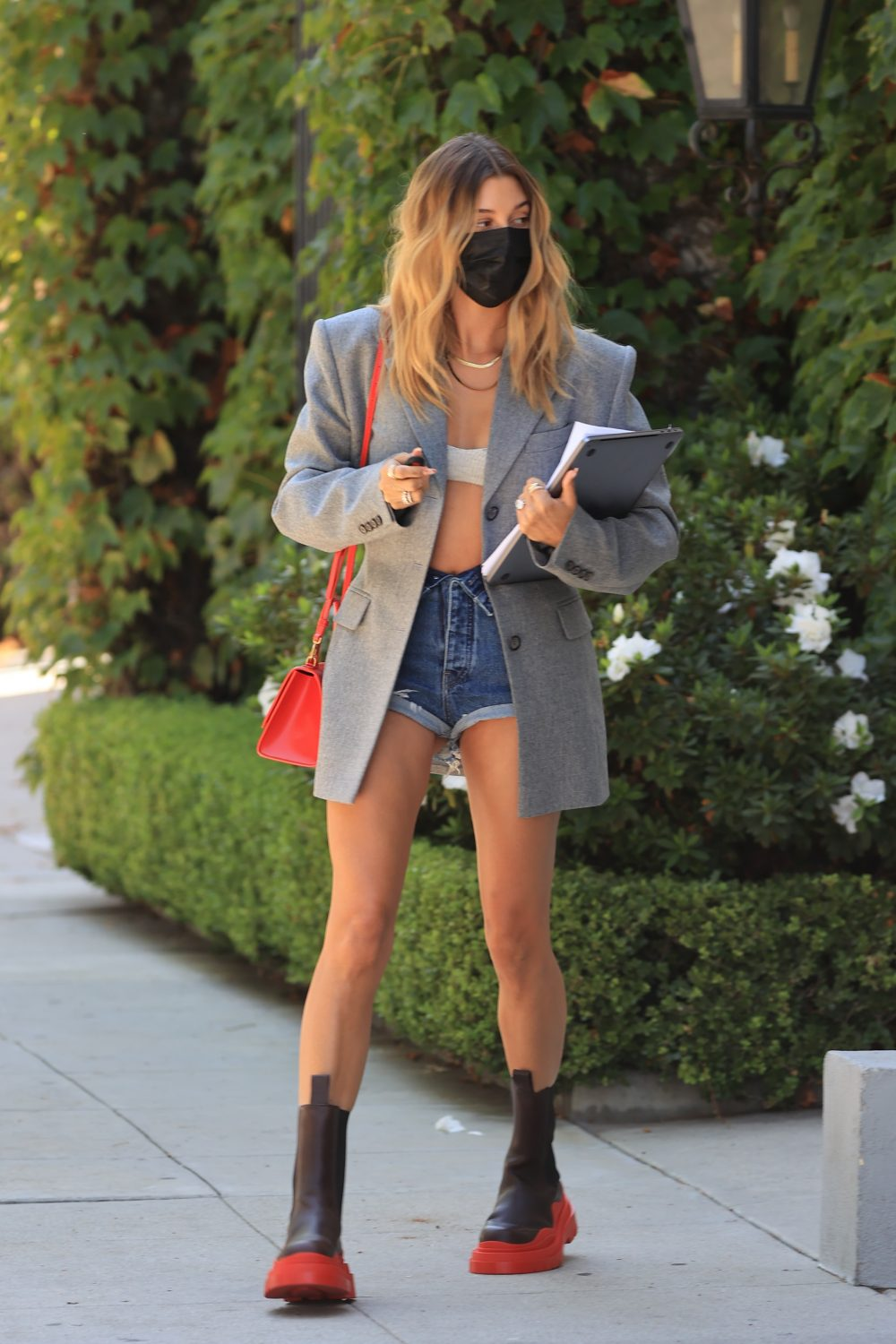 Hailey Bieber rock huge boots with a business attire