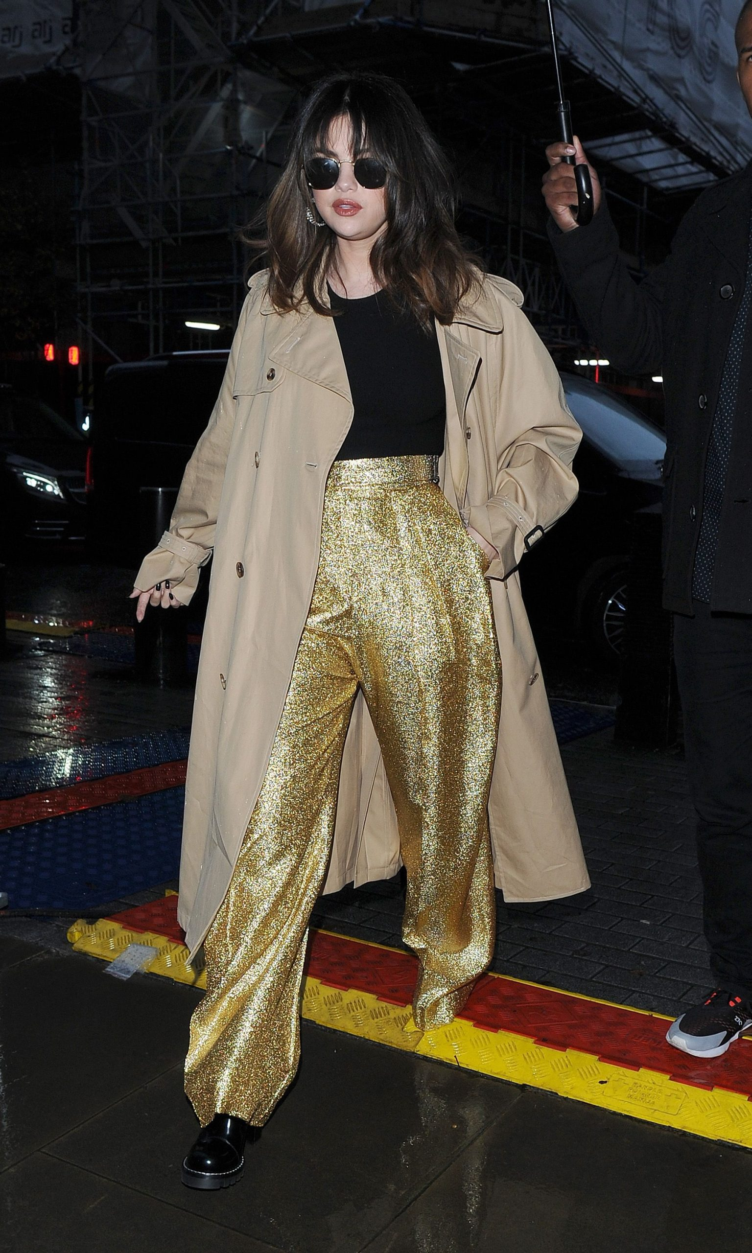 Selena Gomez leaves her hotel, and arrives at the Radio 1 studios, wearing sparkly gold trousers and a tan coloured coat. She completed the look with a pair of sunglasses