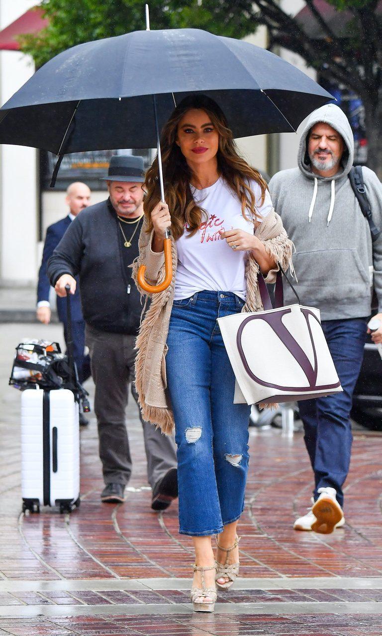 Sofia Vergara stays dry in the light rain with an umbrella