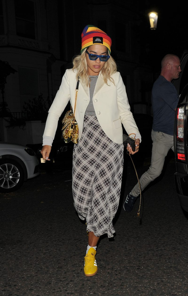 Rita Ora arriving home, having been filming earlier in the day. Rita wore yellow Adidas trainers, a multicoloured striped Marc Jacobs beanie, a patterned dress and a cream jacket, with blue sunglasses finishing off her look.